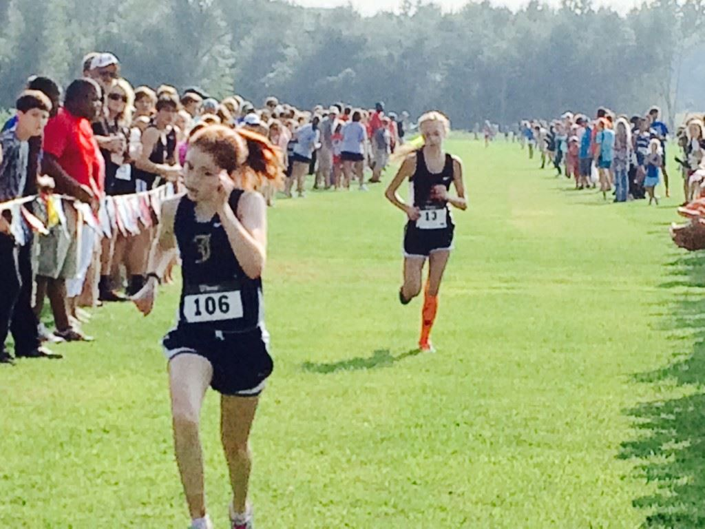 Jacksonville's Rebecca Hearn (106) sprints to the finish ahead of Alexandria's Abby Nunnelly in Saturday's Waffle House/Yellow Jackets Invitational girls race.