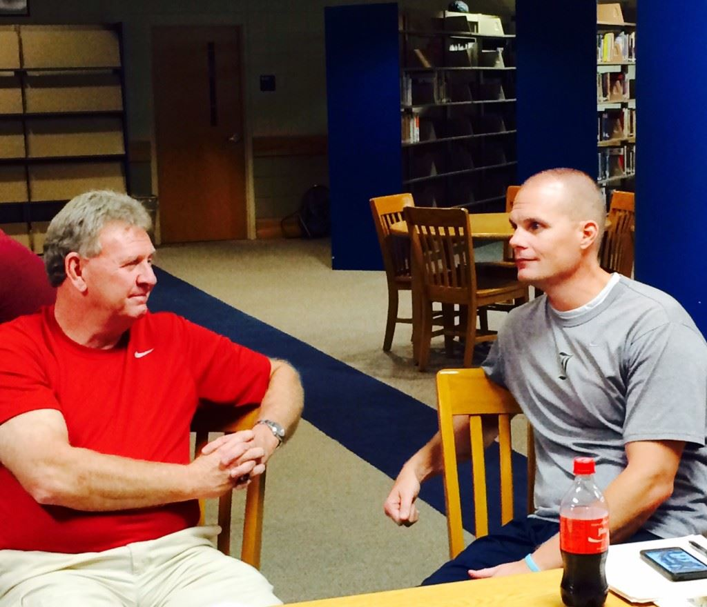 Saks coach Randy Law (L) and Jacksonville's David Clark discuss the affairs of the season while awaiting the results of the Calhoun County Volleyball Tournament seeding meeting Wednesday. Their teams were seeded second and third, respectively, behind No. 1 Oxford.