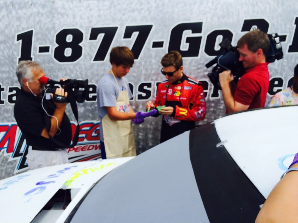 Sprint Cup driver Jamie McMurray (center right) preps White Plains Middle School student Jacob McCulley for applying a green hand print to an old Cup car during a promotional appearance at Talladega Superspeedway Tuesday.