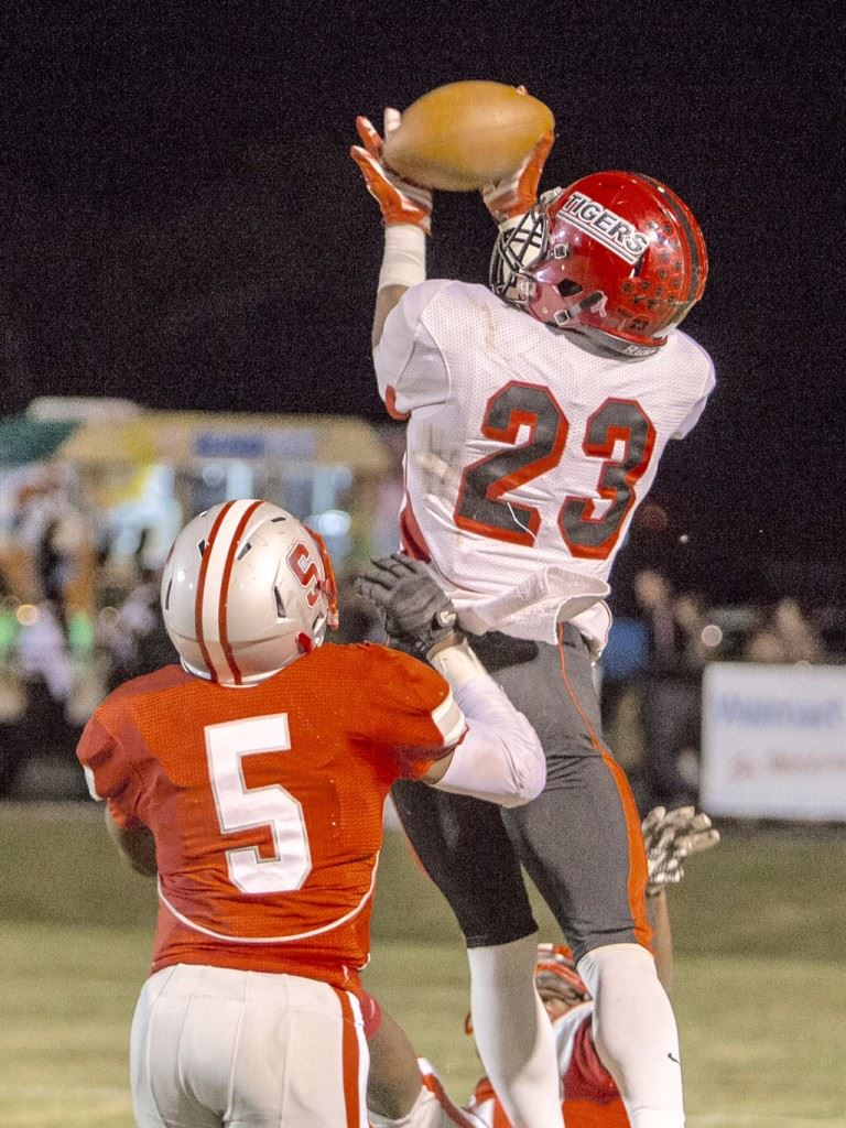 Cleburne County's Jeremiah Blake (23) goes high above Saks' Rodney Reddick to haul in a second-quarter touchdown that drew the Tigers to within 21-16 at halftime Friday. (Photo by Jonathan Fordham)