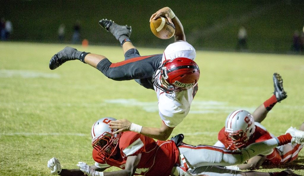 Cleburne County's Json Henson flies over Saks' Quin Smith for more yardage Friday. Henson was the Tigers' leading rusher with 166 yards. (Photo by Jonathan Fordham)