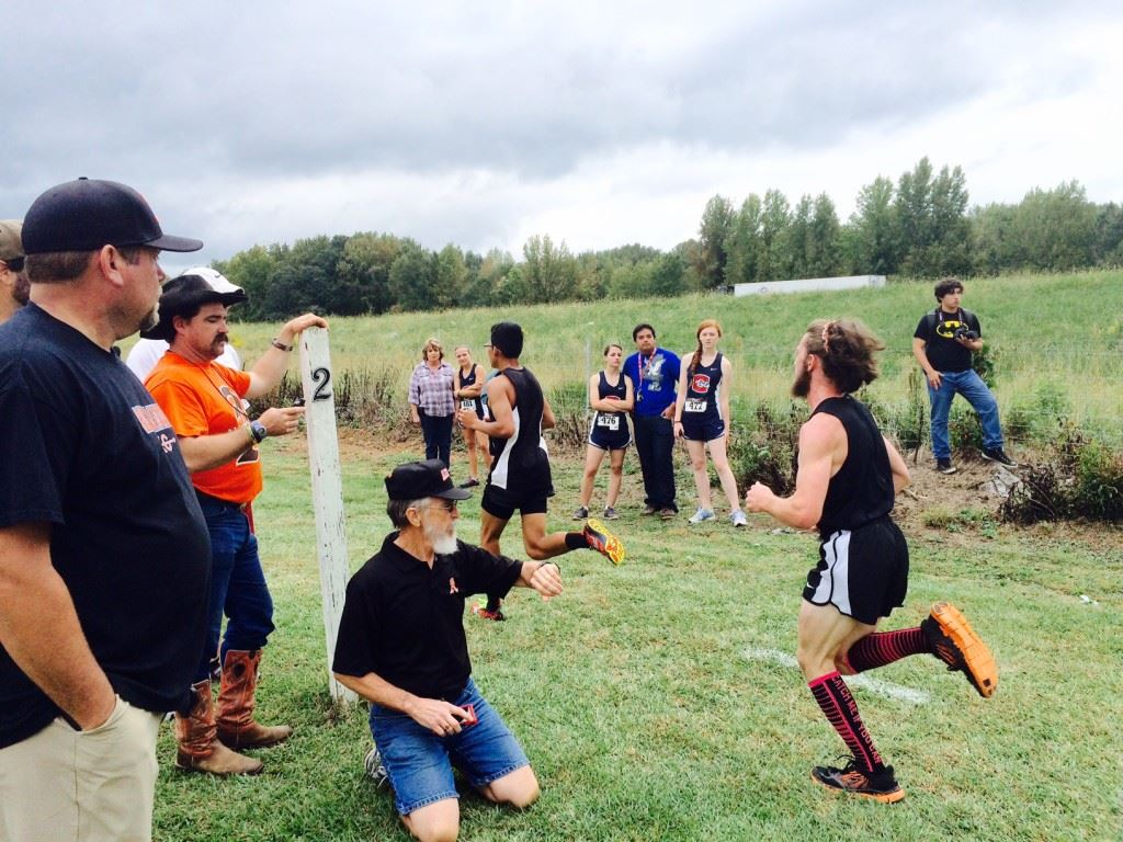 Lane Trapp's dad Shane (orange shirt) checks the time as Lane comes up on the two-mile marker in the Creekbank Invitational.