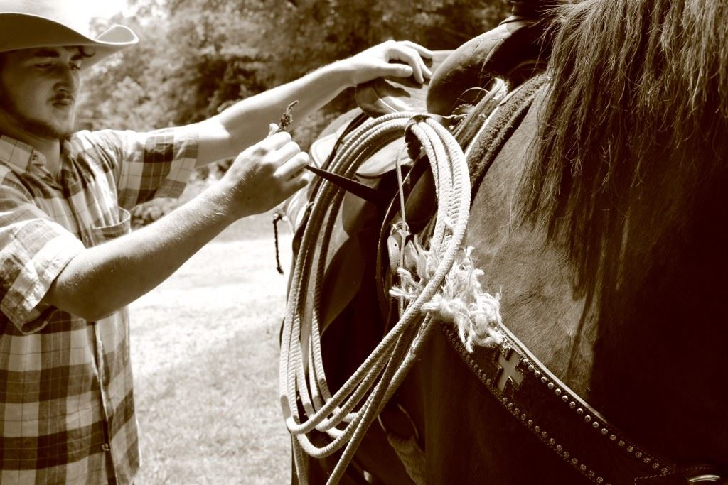 Lane Trapp gets his horse, Dynamite, ready for a ride.