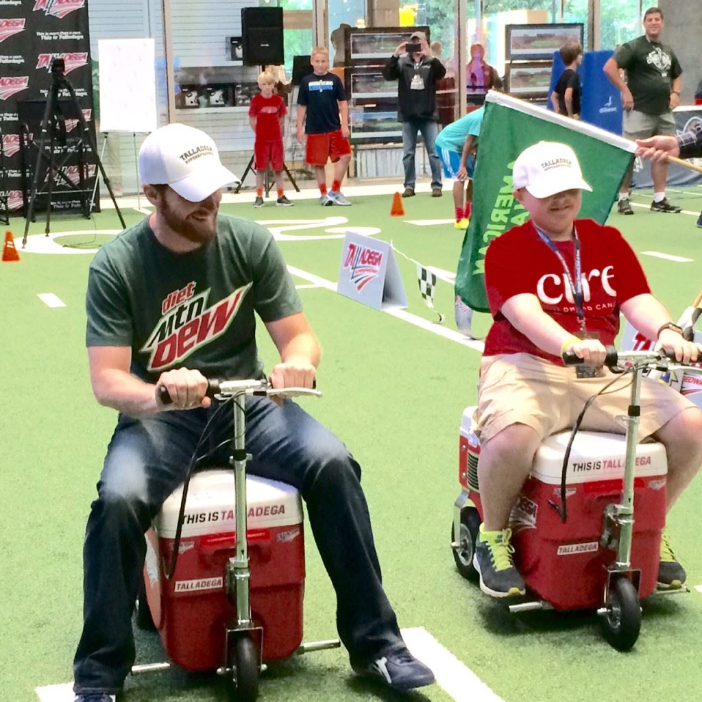 Dale Earnhardt Jr. (L) races sixth-grader Austin Freeman during a promotional appearance at the College Football Hall of Fame. Freeman, a pediatric bone cancer patient, fulfilled a dream by spending the day with his favorite driver.