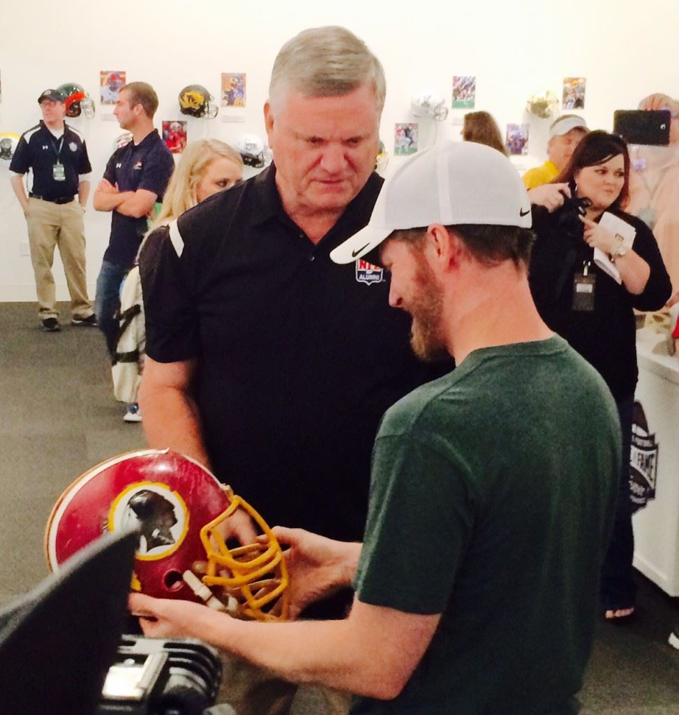 College football Hall of Famer Dave Butz (L) gives Dale Earnhardt Jr. the back story on his Washington Redskins helmet. It was the last helmet Butz wore in an NFL game.