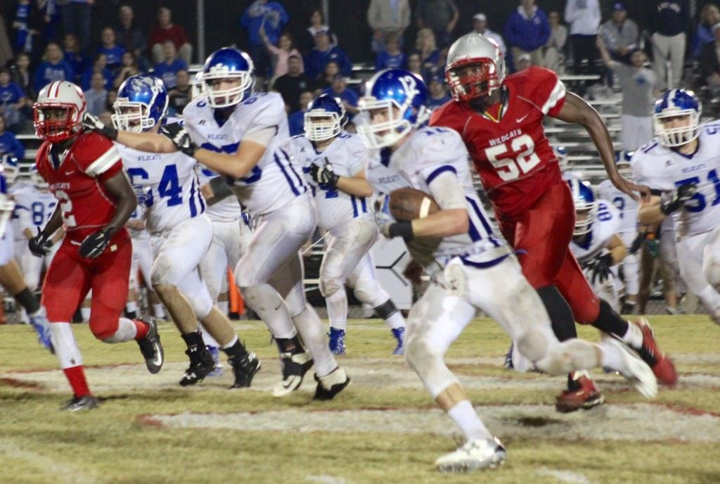 West Limestone quarterback Reed Blankenship runs for yardage as Saks' Demario Burnett (52) tries to chase him down. On the cover Blankenship is trying to escape the grasp of a Saks tackler. (Photos by Ocala Honeycutt)