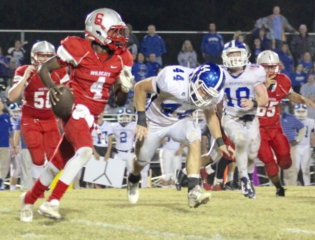 Saks quarterback Quin Smith (4) looks for running room while being pursued by West Limestone's Cody Shedd (44) and Tanner Walker. (Photo by Ocala Honeycutt)