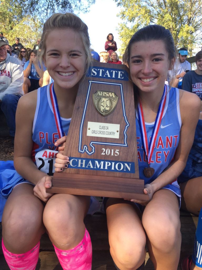 Pleasant Valley's first two finishers, Emma Hood (L) and Juliana Ballew, sit with the state championship trophy. (Photo courtesy of Tara Hood)