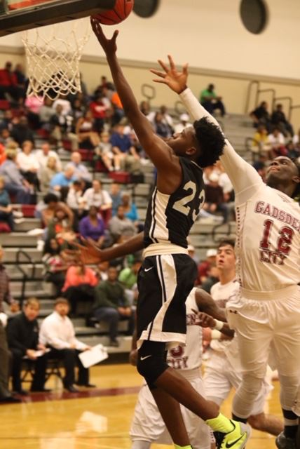 Sacred Heart's Kevion Nolan (23) cuts past the defense of Gadsden City's Denzel Mooney for two of his team-high 18 points. (Photo by Kristen Stringer/Krisp Pics Photography)