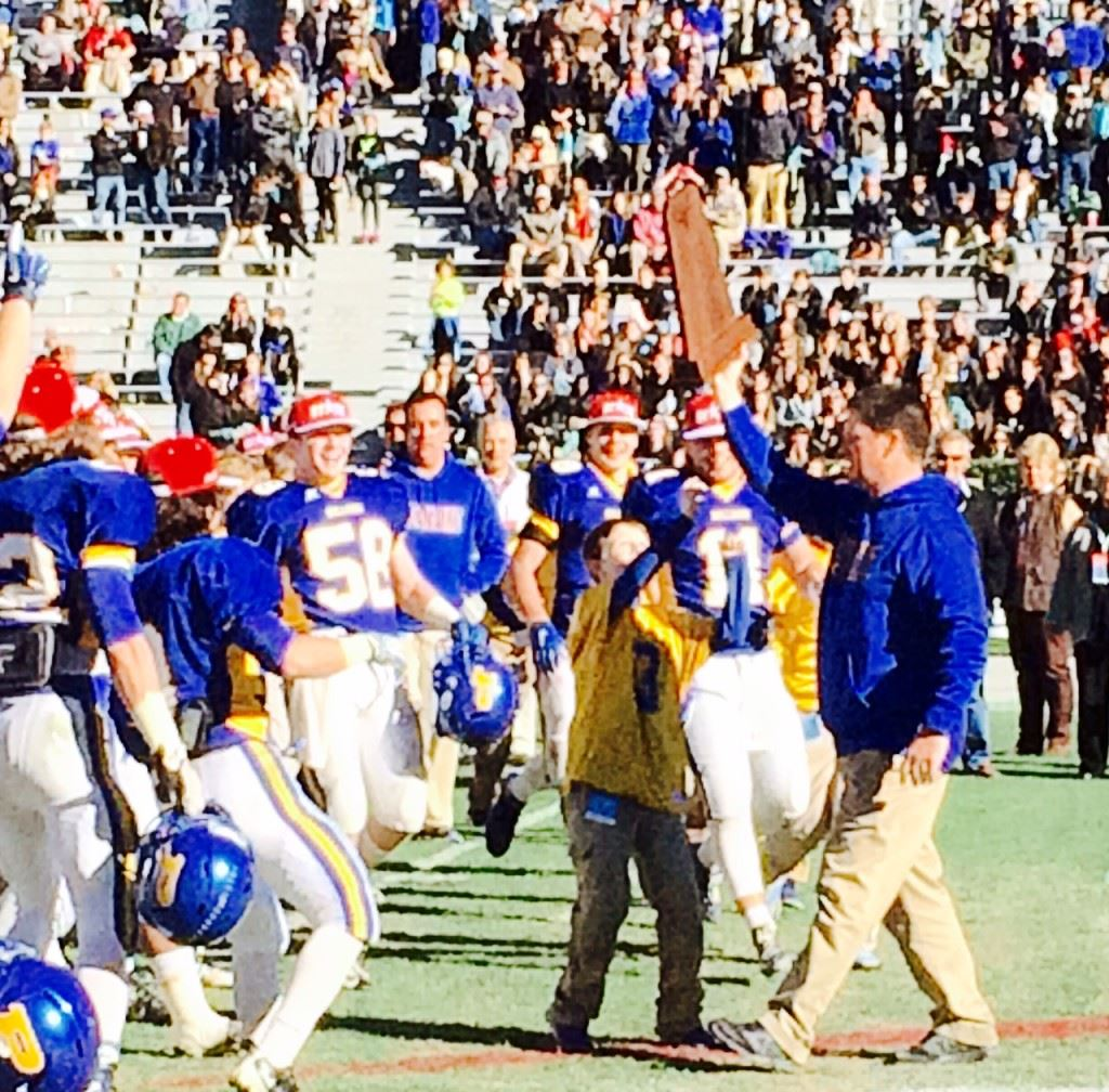 Piedmont coach Steve Smith carries the blue state championship trophy to his awaiting team.