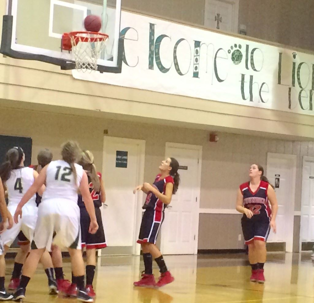 JCA and Faith Christian players stand poised to see if the ball will fall through the hoop or roll off the rim Monday night.