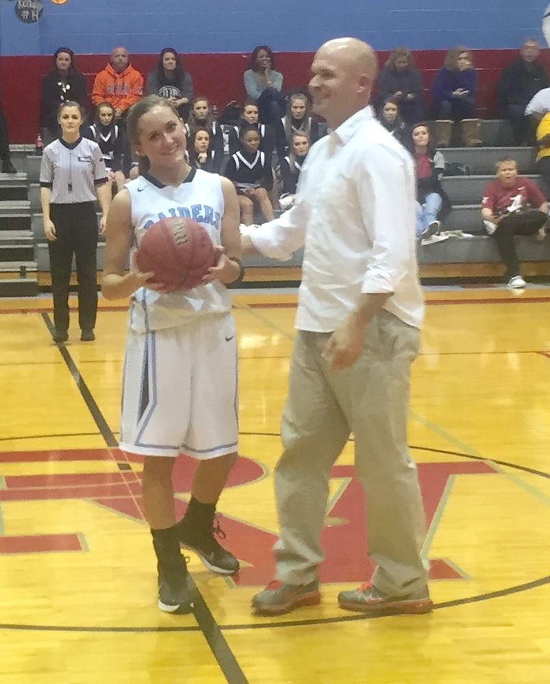 Pleasant Valley girls basketball coach Brad Hood presents the game ball to Atleigh Brannon after the Lady Raiders guard scored the 1,000th point of her career Tuesday night.