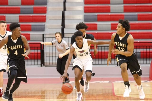 Sacred Heart's Kevion Nolan (23) races up the floor between Carrollton's Jarel Spear (4) and Dylan Parham Saturday. (Photo by Kristen Stringer/Krisp Pics Photography)