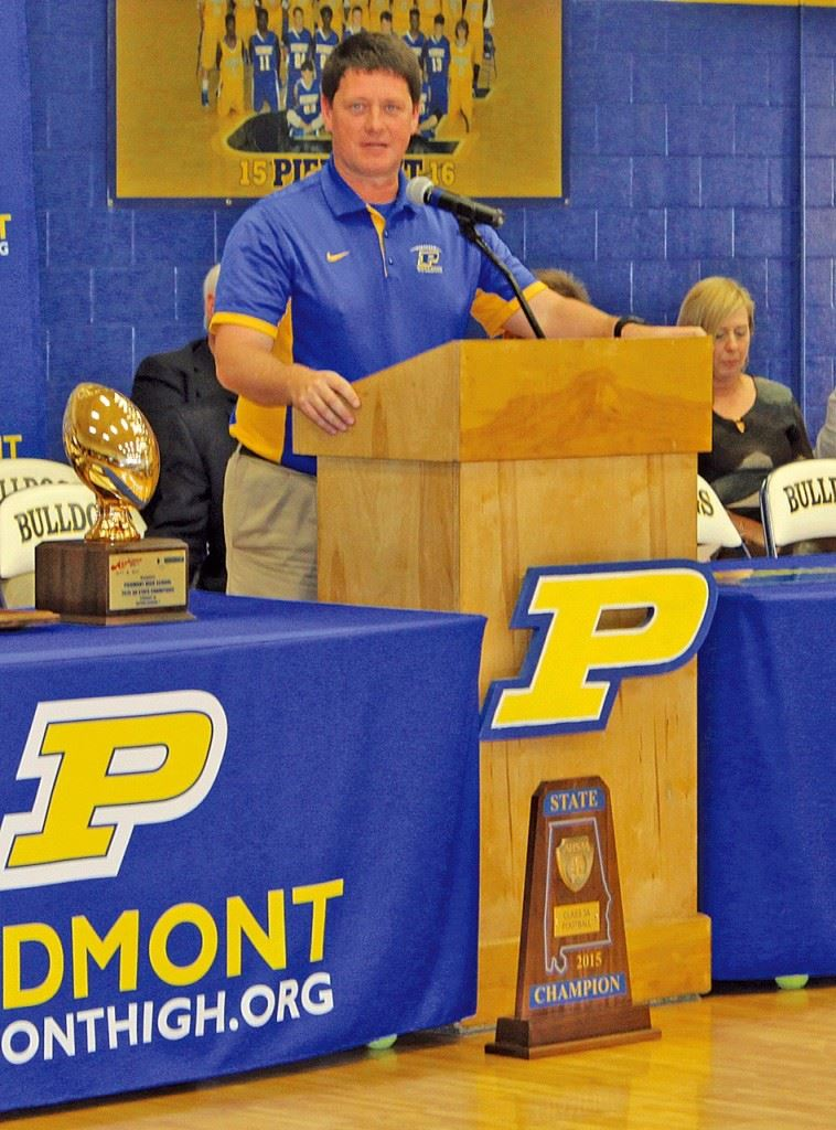 Piedmont coach Steve Smith talks proudly about the accomplishments of this year's Class 3A state championship football team. On the cover, Piedmont mayor Bill Baker displays the marker that proclaims the Bulldogs' two state titles. Below, the Piedmont seniors who helped make this season possible. (Photos by Shannon Fagan/Cherokee County Herald)