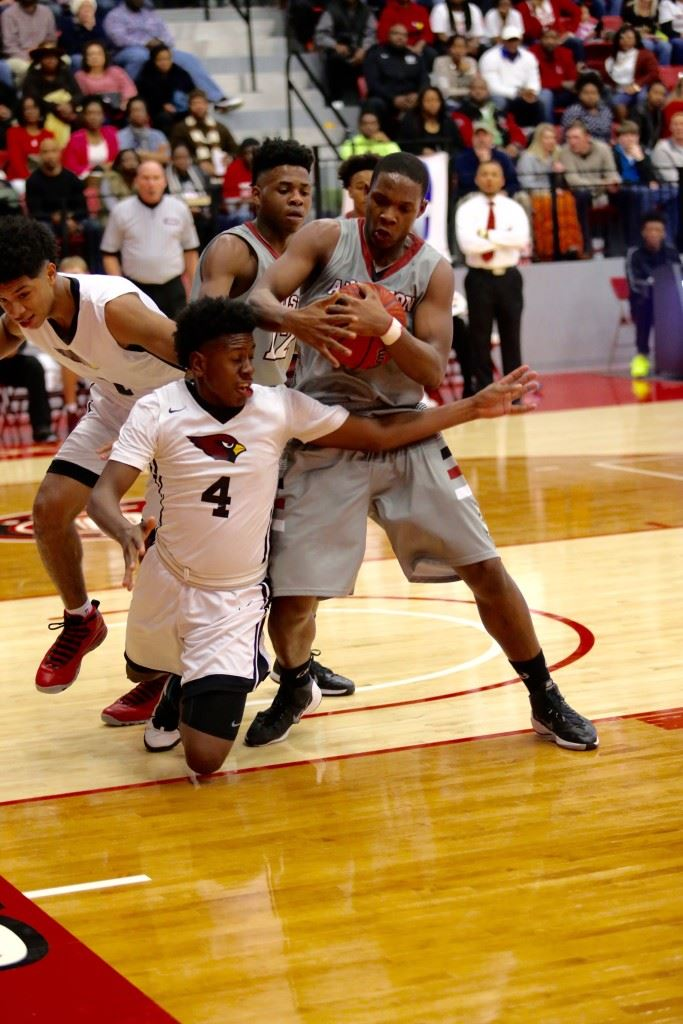 Boys tournament MVP DeQuan Ross takes control of a rebound despite the efforts of Sacred Heart's Murdock Simmons (4) in Saturday's boys County Tournament championship game. (Photo by Kristen Stringer/Krisp Pics Photography)