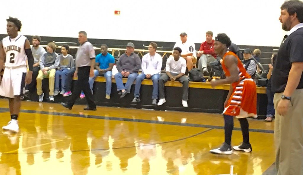 Alexandria's Jamal Tucker (C) stands poised between Lincoln coach Rush Rutledge (R) and Zay Caldwell to receive the ball in the second quarter Thursday. Jamal scored 12 second-quarter points after Luke Tucker (cover) scored the Cubs' first 10.