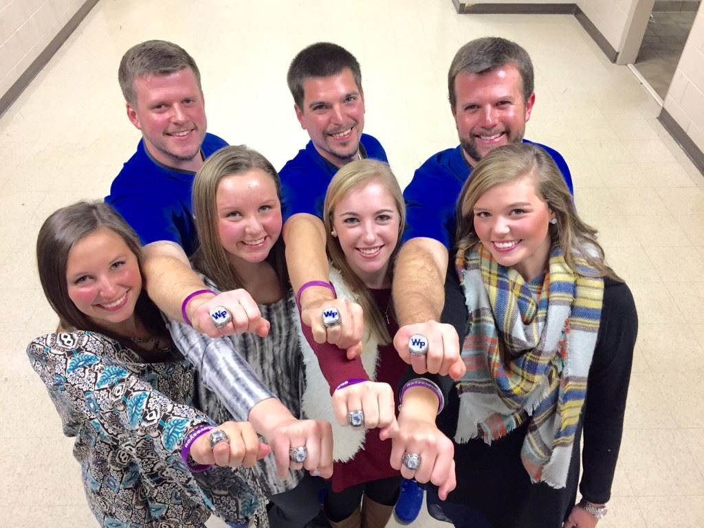 White Plains golf coach Marcus Harrell (second right), his assistant and players show off the state championship rings they had presented Tuesday night.