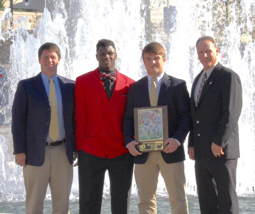 Piedmont quarterback Taylor Hayes (holding plaque) stands with (from left) Bulldogs head coach Steve Smith, 3A Lineman of the Year finalist Neonta Alexander and assistant coach James Blanchard after winning the Class 3A Back of the Year award Wednesday. (Photo by Shannon Fagan)