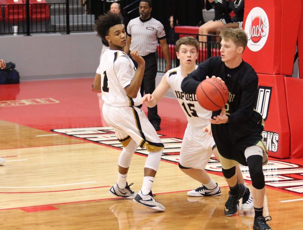 Faith Christian's Caleb McCord (R) looks to leave Oxford's Torry Robertson (1) and Andrew Pratt behind as he tries to start the break Monday. (Photo by Kristen Stringer/Krisp Pics Photography)
