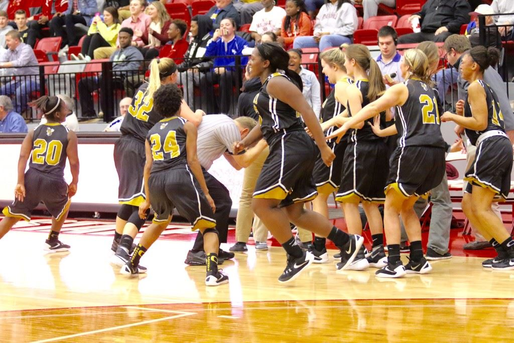 The game official is forced to duck and cover to avoid the Oxford team erupting from the bench celebrating its victory over top-seeded Anniston in overtime. (Photos by Kristen Stringer/Krisp Pics Photography