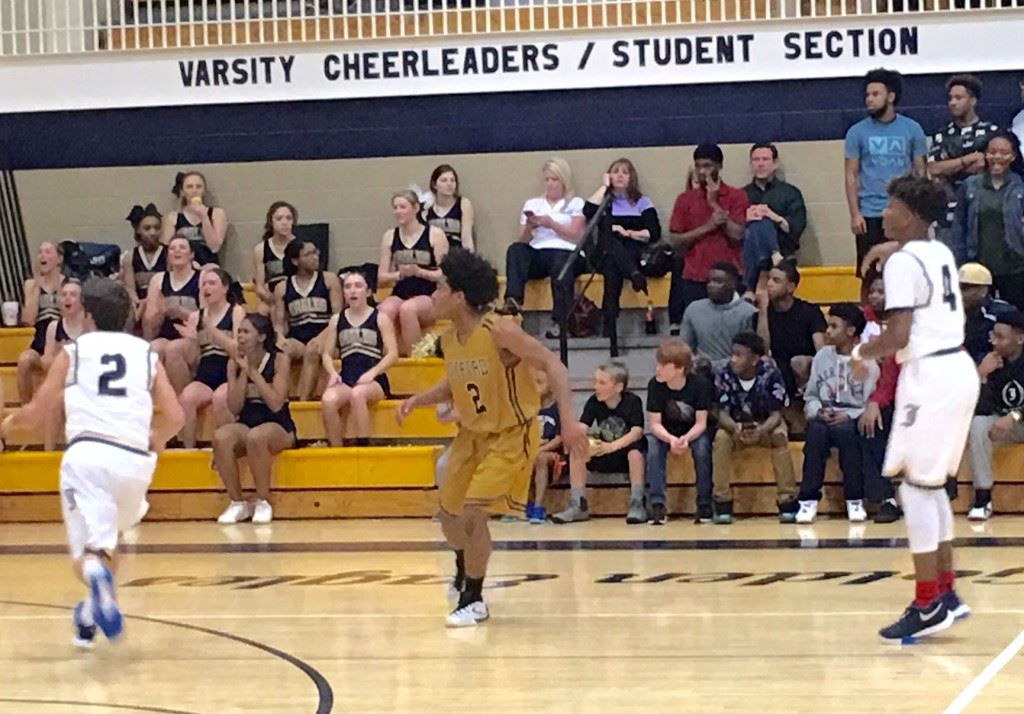 Oxford defensive specialist Jalen Moore (gold 2) was always keenly aware of where Jacksonville's Cam Horton (4) was on the floor Monday night.