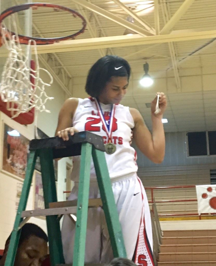 Nothing but net! BryAnna Browning gets her strand as the Saks girls basketball team takes turns cutting the net after winning the area championship Friday night. (Photo by Jason Katz)