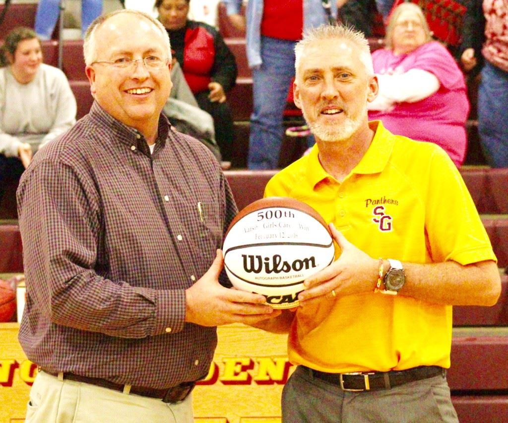 Spring Garden coach Ricky Austin (R) accepts a game ball from principal Mike Welsh commemorating his 500th win with the Spring Garden girls team. On the cover, the Spring Garden fans celebrate the milestone. (Photos by Shannon Fagan)