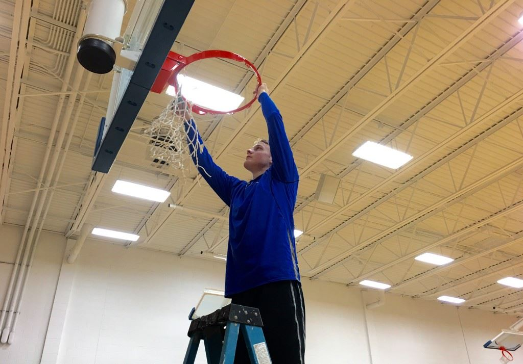 Tournament MVP Bayley Blanchard grabs his piece of the net after leading Piedmont to its second straight area championship. On the cover, Blanchard (21) is joined by teammates (from left) Easton Kirk, Darnell Jackson and Austin Brazier on the all-tournament team.
