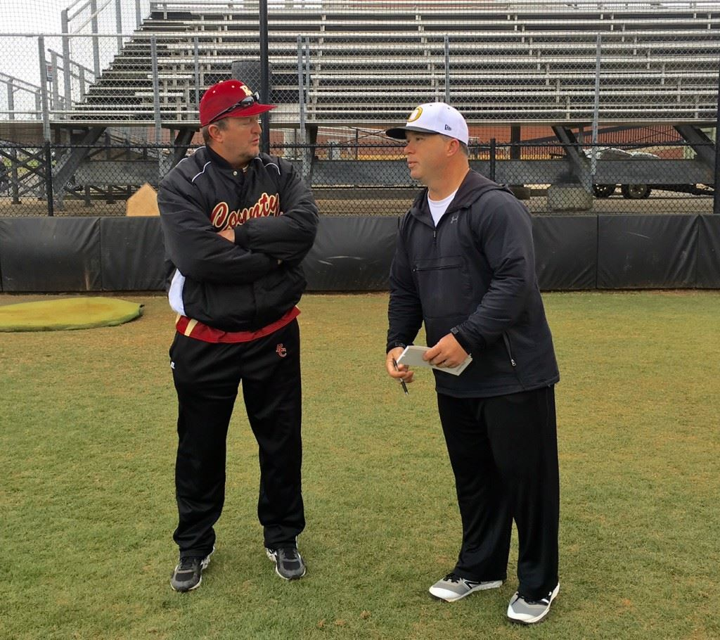 Oxford baseball coach Wes Brooks (R) talks with Russell County coach Tony Rasmus before the rain came in their Opening Day game Monday.