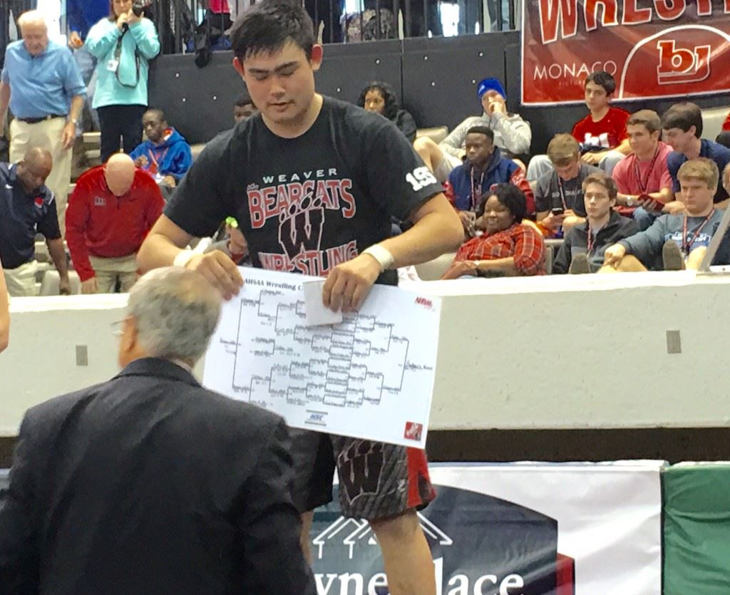 Weaver senior Chase Rodgers accepts a copy of the Class 1A-5A 195-pound bracket he won from AHSAA executive director Steve Savarese.