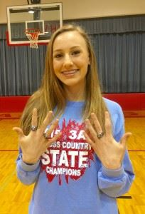 Rachel Faucett displays her three state championship rings, the newest two she received Tuesday.