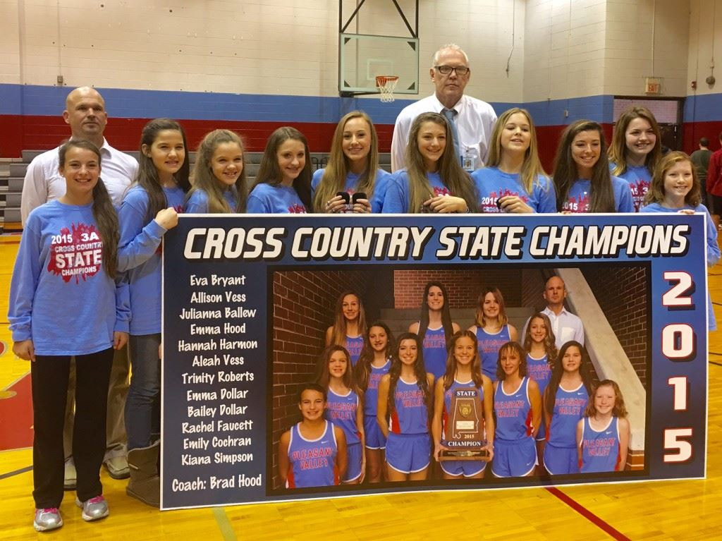 Pleasant Valley's state champion girls cross country team, along with coaches Brad Hood (L) and Rex McAllister, stand with the sign that will hang in the gym to commemorate their feat. On the cover, the team shows off its championship rings. (Cover photo by Emily Harrell)