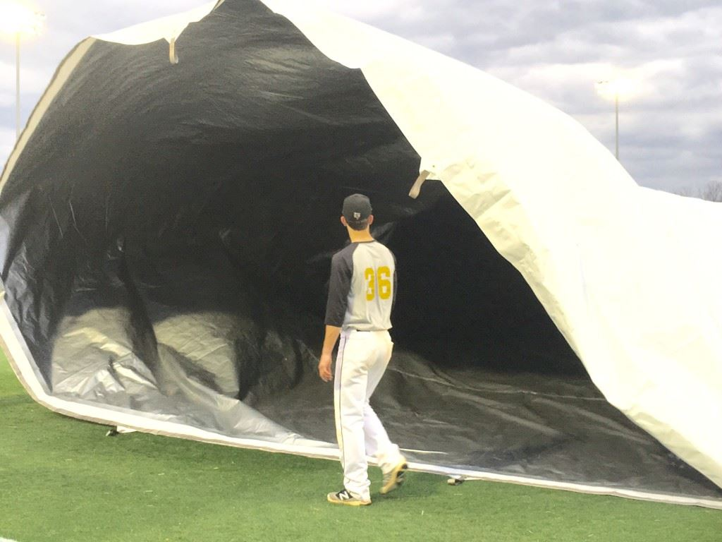 County baseball tournament MVP Andy Hammond holds on to his end as the Yellow Jackets learn to roll out the new tarp for the signature baseball field at Choccolocco Park.