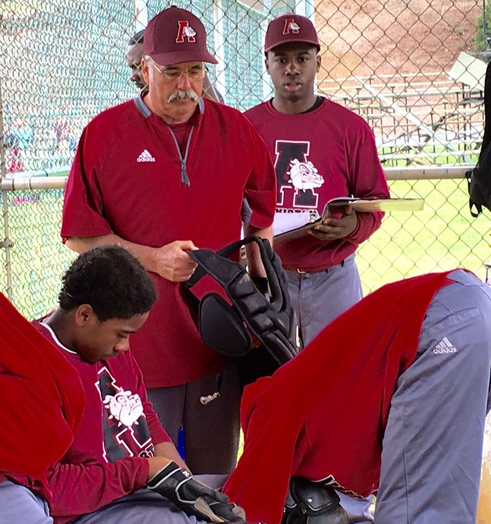 Anniston baseball coach Paul Farlow watches as catcher Jimmy Felton gets his gear on between innings. On the cover, the Bulldogs huddle to break down the day's game.