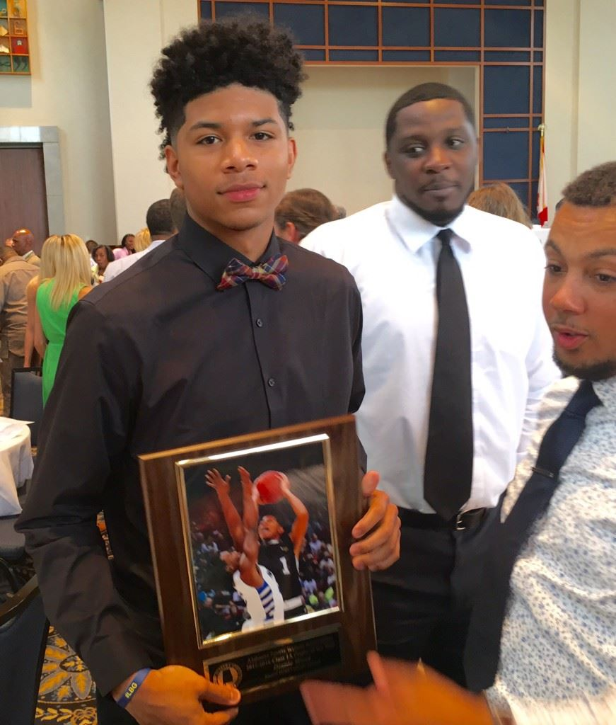 Sacred Heart sophomore Diante Wood displays his award for being named Alabama's Class 1A Boys Player of the Year. On the cover, 1A finalists Tykeah Rogers of Spring Garden (L) and Wood in action. (Cover photos by Kristen Stringer/Krisp Pics Photography)