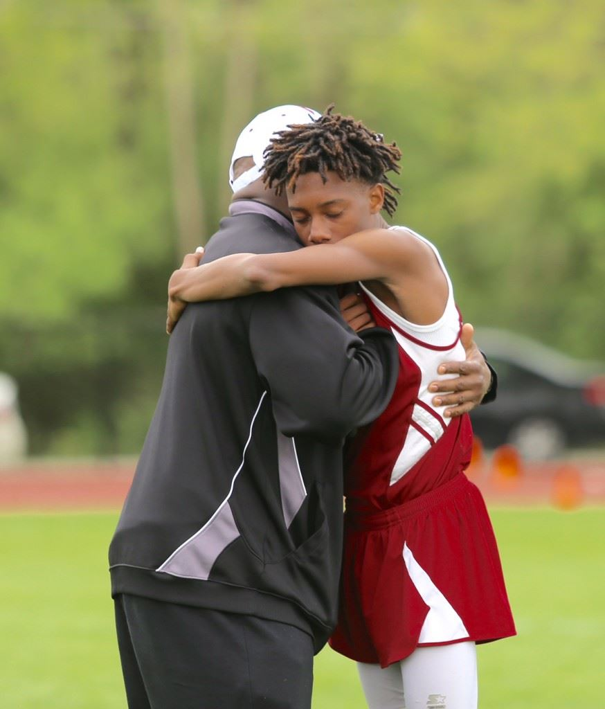 Anniston senior Leonard Brown embraces assistant coach Leroy Clark after an emotional run in Tuesday's Calhoun County Track Meet. On the cover, Leonard (R) and younger brother Nick dedicated their effort in the meet to the memory of their mother, who passed away earlier in the day. (Photo by Kristen Stringer/Krisp Pics Photography).