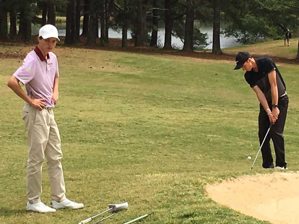 Donoho's Jacob Lecroy (L) waits patiently as White Plains' Layton Bussey chips over the greenside bunker on 18 for an eagle that gave him a 3-under-par 69 Friday.