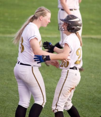Taylor Davenport (R) can't contain her excitement as she celebrates her walk-off homer with teammate Brantli Champion. On the cover, the Oxford bench empties to greet Bailey Clark after her second-inning home run. (Photos by B.J. Franklin/GungHo Photos)