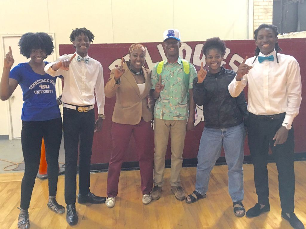 Anniston track coach Lisa Howard (third from left) stands with the five Bulldogs who signed college scholarship letters Monday.