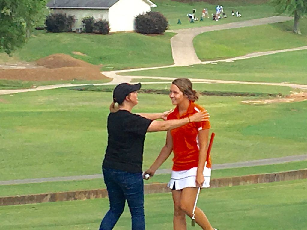 Alexandria's Abby Stevens is greeted by her mother after sinking a long birdie putt in a playoff to earn a spot in the state tournament.