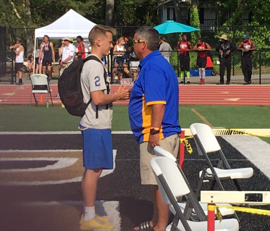 Piedmont pole vaulter Will Mitchell (L) and his dad, Bulldogs coach Mark Mitchell, talk about the day's jumps.