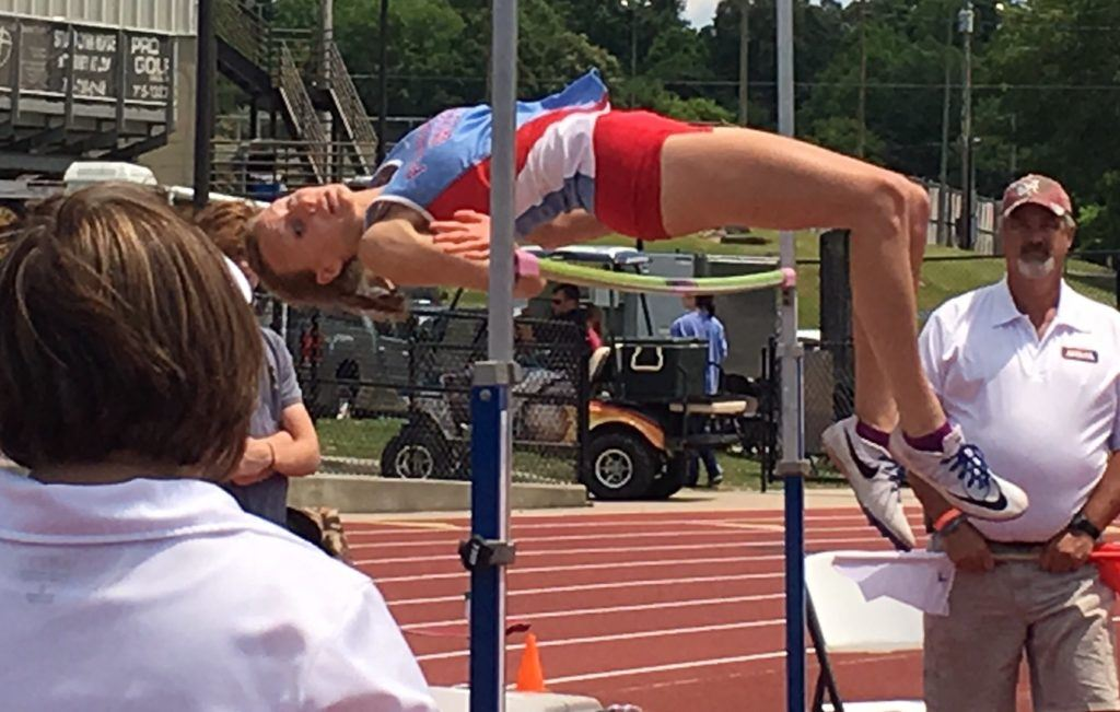 Pleasant Valley's Rachel Faucett clears the bar at 5-2 on her way to a third straight state high jump title. Below, she reviews the video of her winning jump.