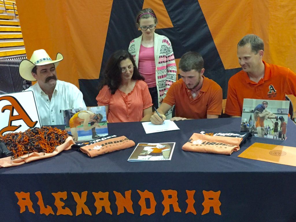 Alexandria senior Lane Trapp signs a wrestling scholarship with Lourdes University as his family and Valley Cubs coach Frank Hartzog look on.