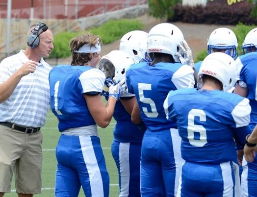 White Plains head coach Chris White leans into the Wildcats' huddle to relay a play.
