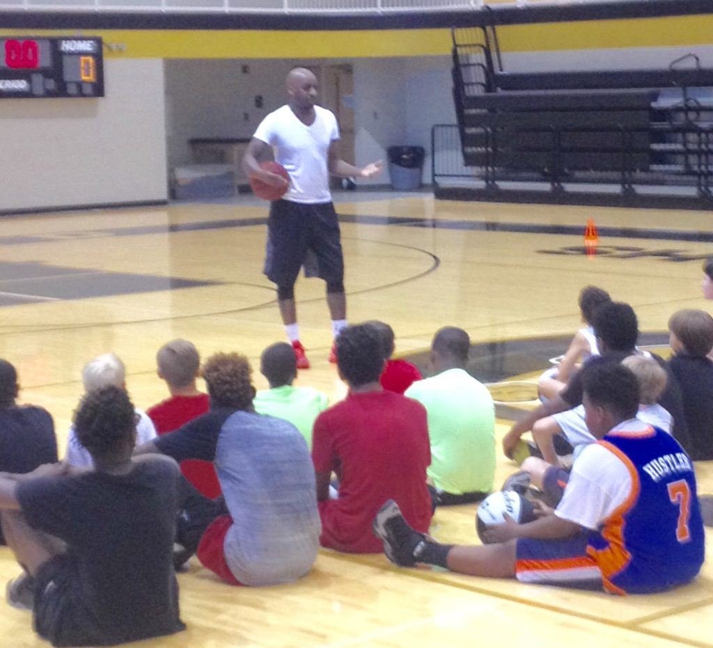 Former NBA point guard Walker D. Russell talks to the campers at the conclusion of Oxford's fifth annual basketball camp Friday.