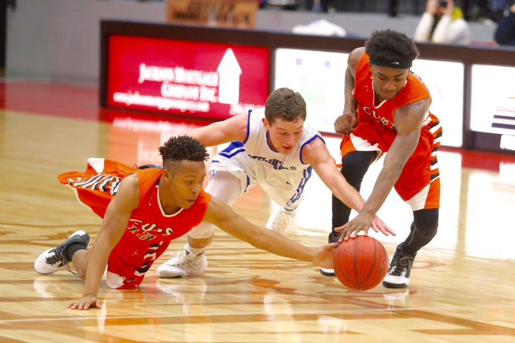 White Plains guard Jerod Guthrie (center) dives for a loose ball between two Alexandria players at this season's Calhoun County Tournament.