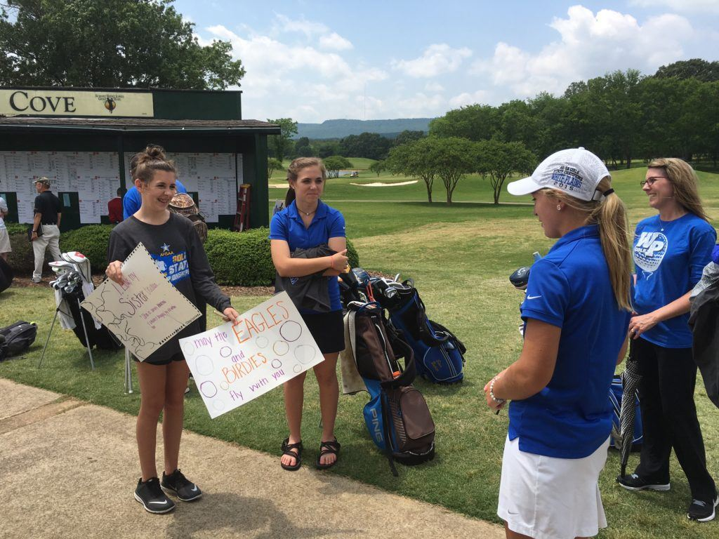 White Plains senior Morgan Prickett checks out the posters her family made after her final high school round in the state tournament Tuesday.