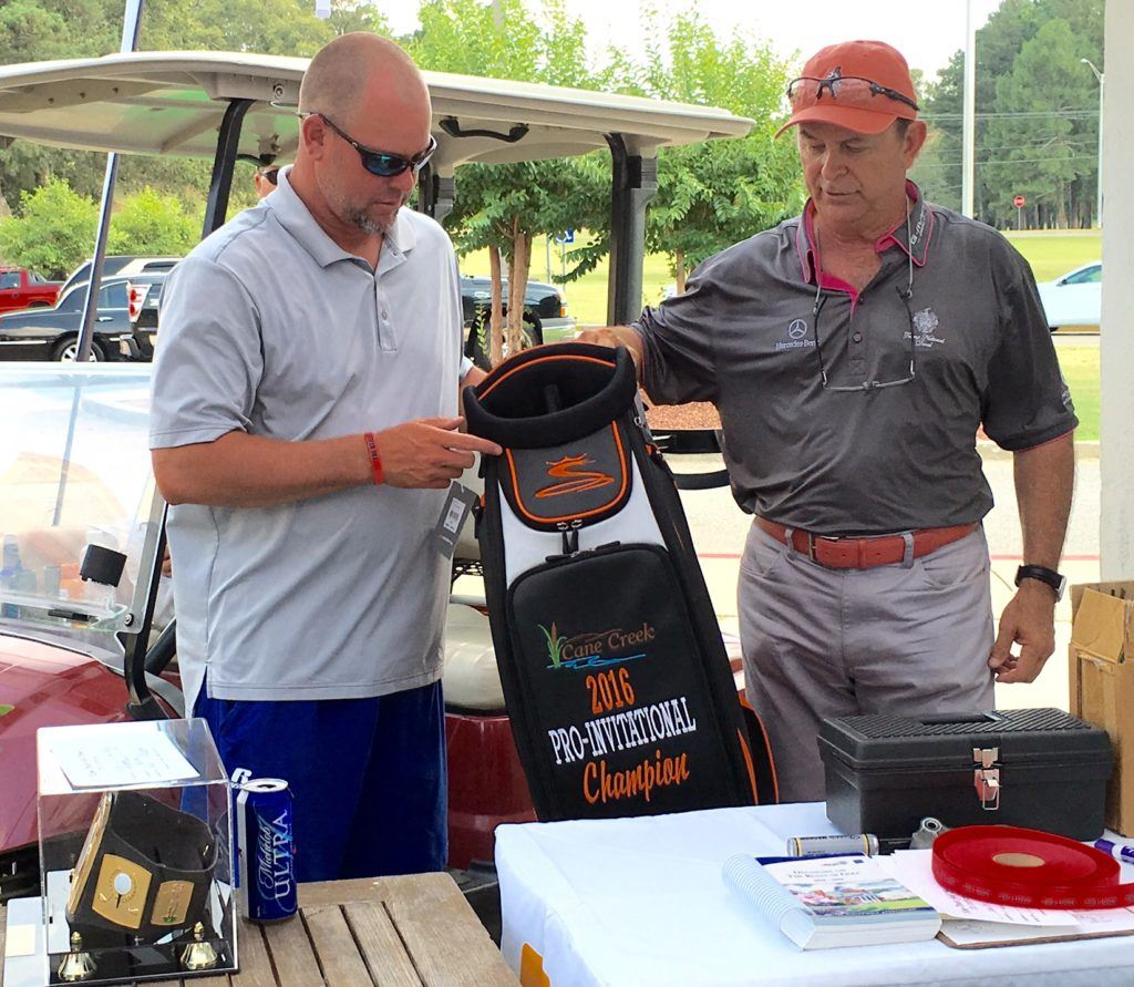 Medalist Ty Cole (L) checks out the golf bag presented by Cane Creek pro Kenny Szuch for winning the flight winners playoff in the Pro-Invitational Sunday.