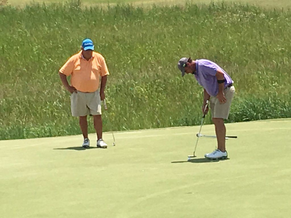 Chad Calvert (L) watches Chad Reavis putt on the 16th green during Saturday's first round of the Silver Lakes Championship.