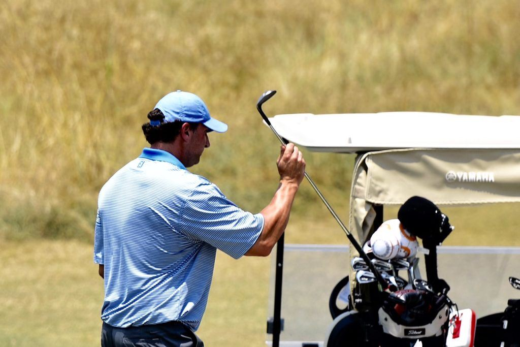 Chase Thomas pulls a club before continuing his round Sunday. (Photo by Sandra Howell)